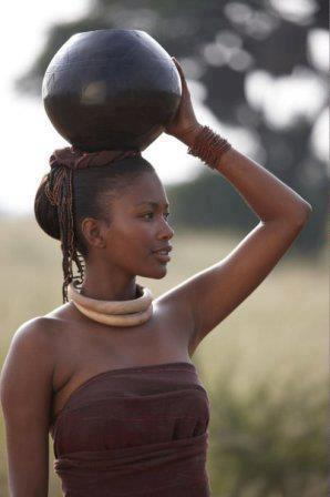 A pretty slim African girl carrying a clay pot on her head in a Kenyan village